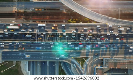 Beautiful top view to autonomous cars self-driving on multi-level highway in Moscow. Picturesque aerial panorama of the road traffic in a big city on the evening.