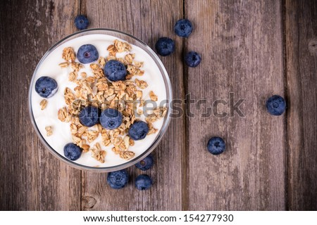 Yogurt with granola and fresh blueberries, in glass bowl over old wood background. Vintage effect. #154277930
