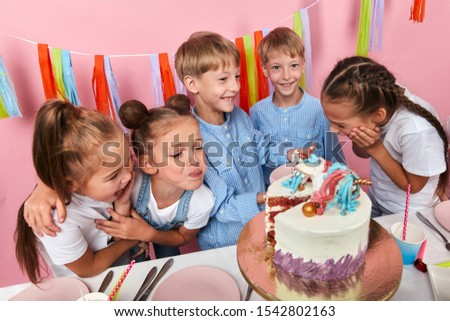 funny laughing children sharing pieces of cake, isolated pink background, studio shot, childhood. studio shot #1542802163
