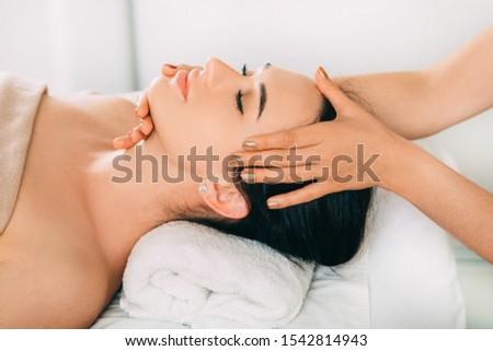 Woman enjoying head massage, face close-up. Relaxing anti-stress massage, treatment head pain #1542814943
