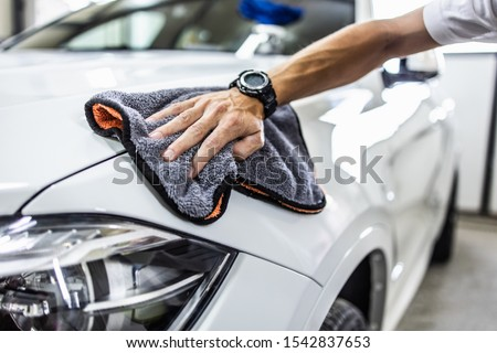 A man cleaning car with microfiber cloth, car detailing (or valeting) concept. Selective focus. Royalty-Free Stock Photo #1542837653