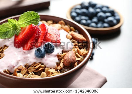 Delicious yogurt with granola and berries served on grey table, closeup #1542840086