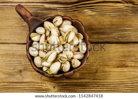 Pistachio nuts in ceramic bowl on a wooden table. Top view #1542847418