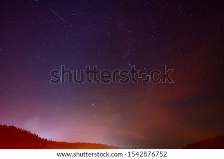 Shooting star or meteoroid over Sirius and Constellation Orion in the night sky.