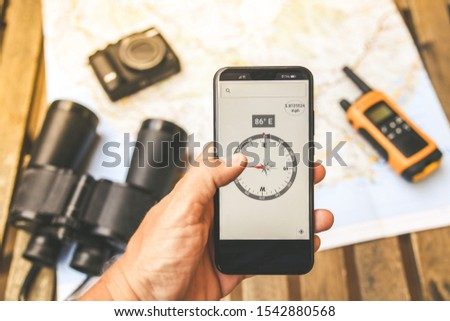 Man hand with electronic compass on smartphone, adventurous objects in background. Walkie talkie, binoculars and camera over a map ready for planning a travel route. Travelling, tech adventure concept #1542880568