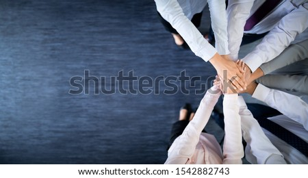 Close up top view of young business people putting their hands together. Stack of hands. Unity and teamwork concept. #1542882743