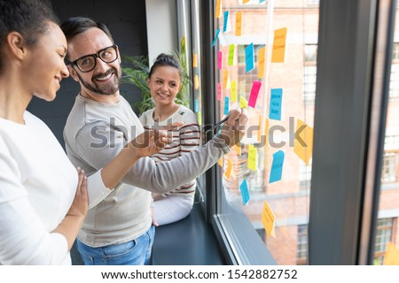 Business people meeting at office and use post it notes to share idea. Brainstorming concept. Sticky note on glass wall. #1542882752