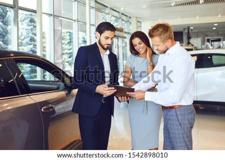 A couple buys a car in a car showroom. #1542898010