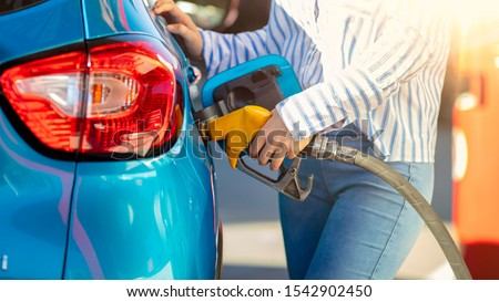 Pumping gas at gas pump. Woman refuel the car. Woman  at the petrol station. Woman filling her car with petrol at gas station. Pumping fuel in to the tank. Detail Of woman Filling Car With Diesel #1542902450