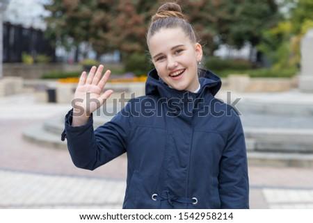 Teenager girl waves her hand, says hello or says goodbye. #1542958214