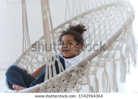 Pleasant African American child resting in swing chair at home #1542964364
