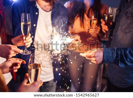 Group of happy people holding sparklers at party and smiling. Young people celebrating New Year together. Friends lit sparklers. Friends enjoying with sparklers in evening. Blur Background. #1542965627