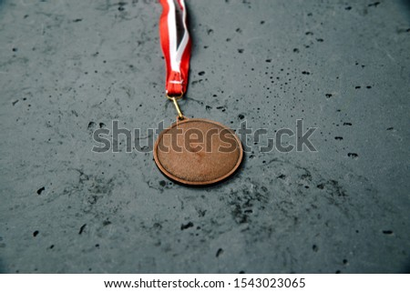 Bronze Medal lie on a stone background. Bronze medal on a dark background. The concept of tournaments and competitions. Victory, winning competitions. #1543023065