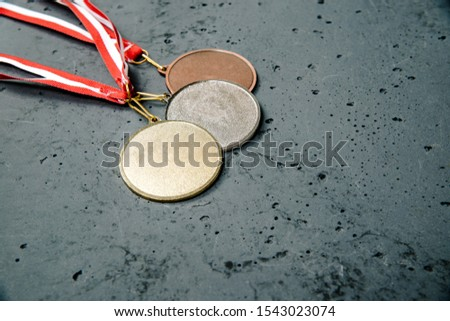The medals lie on a dark stone background. Gold, silver and bronze medal on a dark background. The concept of tournaments and competitions. Victory, winning competitions. #1543023074