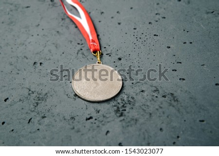 Silver Medal lie on a stone background. Silver medal on a dark background. The concept of tournaments and competitions. Victory, winning competitions. #1543023077