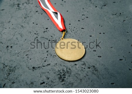 Gold Medal lie on a stone background. Gold medal on a dark background. The concept of tournaments and competitions. Victory, winning competitions. #1543023080