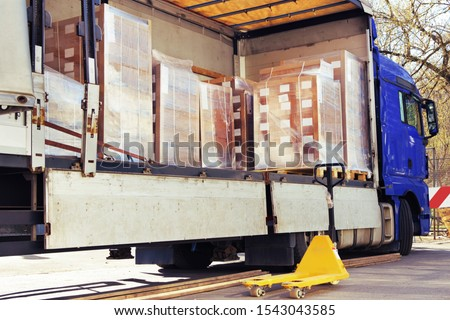The side curtain of the trailer is opened and the truck is full of pallets with merchandise. There are cardboard boxes wrapped with stretch wrap, the pallet jack is waiting beside to unload the cargo. #1543043585