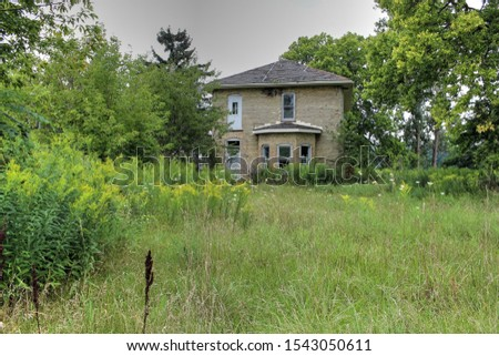 A stock photo showing an old abandoned yellow brick house on an overgrown lot.  #1543050611