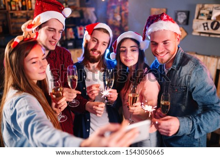 Holiday group selfie. Group of young friends having fun at New Year's Eve party and making crazy faces and taking selfies. Group of beautiful young people in Santa hats.
