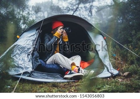 photographer tourist traveler take photo on camera in camp tent in foggy rain forest, hiker woman shooting mist nature trip, trekking tourism, rest vacation concept camping holiday
