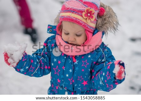 Baby girl in warm clothes in a snow-covered shapes of snow in the winter. #1543058885