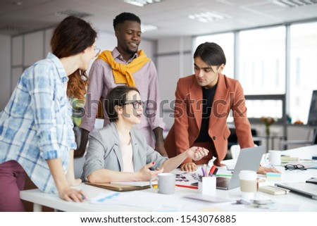 Portrait of young creative business team discussing design project during meeting in office, copy space #1543076885