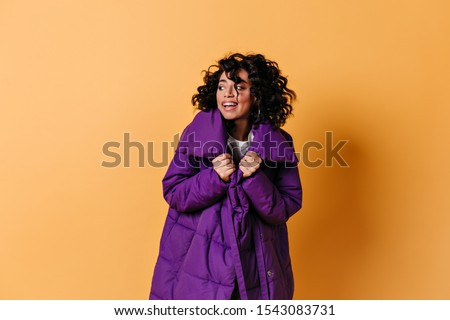 Studio shot of mixed race girl in purple down jacket. Dreamy curly young woman isolated on yellow background. #1543083731
