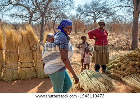 african woman carry child in the back in a traditional way in a blanket #1543110473