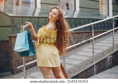 Beautiful girl in a summer city. Lady with shopping bags #1543131452