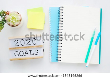 2020 on wood box, blank notebook paper on white marble table background, 2020 new year mock up, template with copy space for text, top view #1543146266