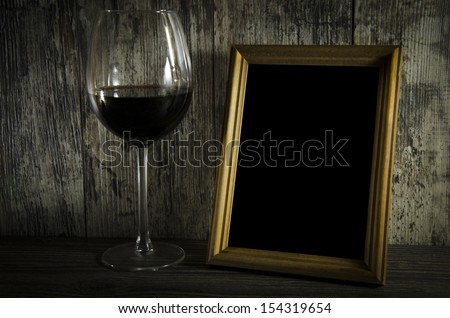 old photo frame on the wooden table with groceries old red wine