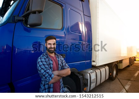 Professional truck driver with crossed arms standing by his semi truck. Trucker occupation and transportation services. #1543212515