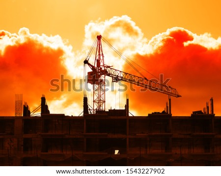 Construction crane building house during dramatic sunset backdrop #1543227902
