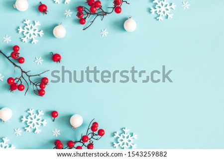 Christmas or winter composition. Snowflakes and red berries on blue background. Christmas, winter, new year concept. Flat lay, top view, copy space #1543259882