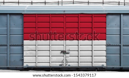 Front view of a container train freight car with a large metal lock with the national flag of Indonesia.The concept of export-import,transportation, national delivery of goods and rail transportation #1543379117