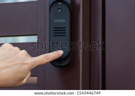 A woman presses the bell button on the front door #1543446749
