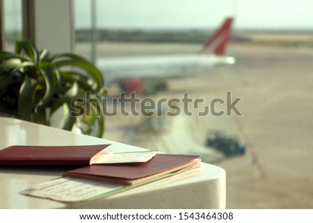 Passports and boarding passes on a table in an airport lounge against the blurred airplane and tarmac window view. #1543464308