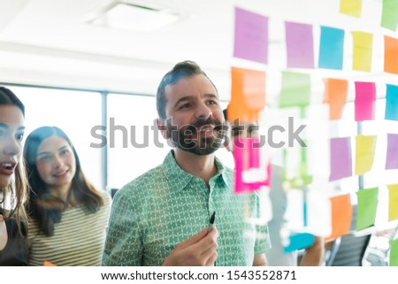 Confident leader discussing over adhesive notes with team at office #1543552871