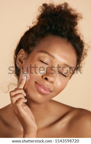 Face skin care. Woman applying cosmetic cream on clean hydrated skin portrait. Beautiful happy smiling african americangirl model with natural makeup applying facial moisturizer, beauty product #1543598720