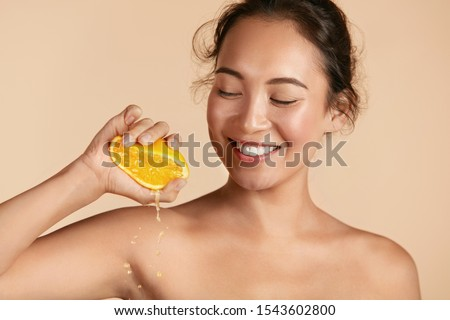 Beauty. Woman with radiant face skin squeezing orange in hand portrait. Beautiful smiling asian girl model with natural makeup, glowing facial skin and citrus fruit. Vitamin C cosmetics concept Royalty-Free Stock Photo #1543602800