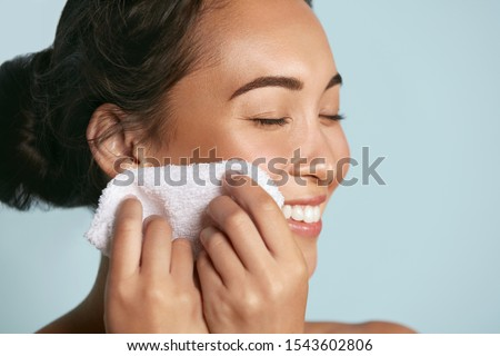 Woman cleaning facial skin with towel after washing face portrait. Beautiful happy smiling young asian female model wiping facial skin with soft towel, removing makeup. High quality studio shot #1543602806