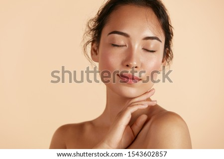Beauty face. Woman with natural makeup and healthy skin portrait. Beautiful asian girl model touching fresh glowing hydrated facial skin on beige background closeup. Skin care concept #1543602857