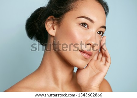 Skin care. Woman with beauty face and healthy facial skin portrait. Beautiful asian girl model with natural makeup touching glowing hydrated skin on blue background closeup. High quality image #1543602866