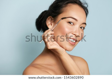 Beauty. Smiling woman brushing eyebrows with makeup brush closeup. Portrait of beautiful happy asian girl model doing make up, shaping brows with cosmetic brush in studio. #1543602890