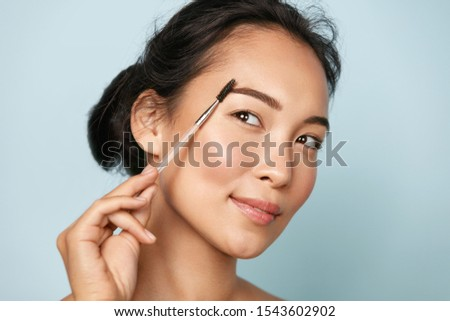 Beauty. Smiling woman brushing eyebrows with makeup brush closeup. Portrait of beautiful happy asian girl model doing make up, shaping brows with cosmetic brush in studio. #1543602902