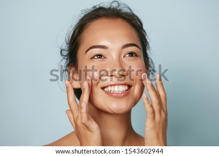 Beauty face. Smiling asian woman touching healthy skin portrait. Beautiful happy girl model with fresh glowing hydrated facial skin and natural makeup on blue background at studio. Skin care concept #1543602944