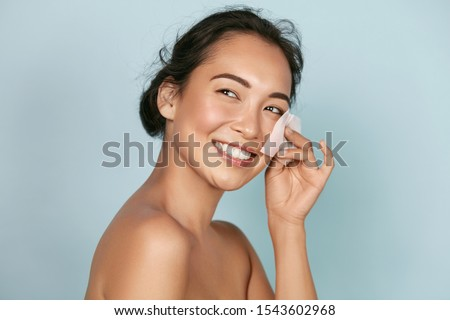 Face skin care. Smiling woman using facial oil blotting paper portrait. Closeup of beautiful happy asian girl model with natural makeup using oil absorbing sheets, beauty product at studio #1543602968