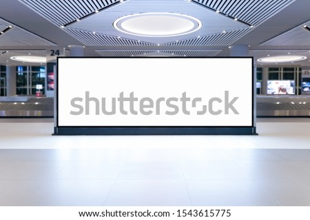Blank advertising billboard in the Airport, blank billboards public commercial with plane passengers. #1543615775