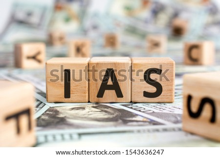 IAS - acronym from wooden blocks with letters, abbreviation IAS International Accounting Standards concept, random letters around, money background #1543636247