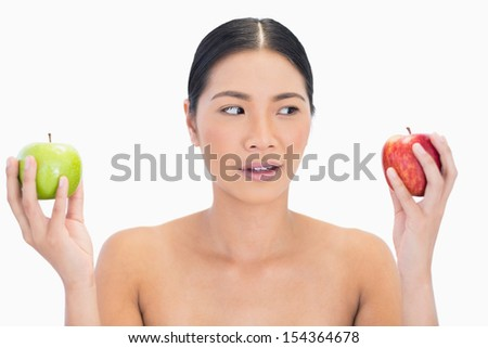 Curious black haired model holding apples in both hands on white background #154364678